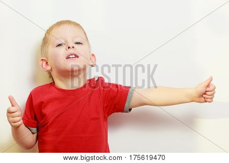 Childhood kids imagination and gestures concept. Little young boy playing having fun showing thumb up gesture