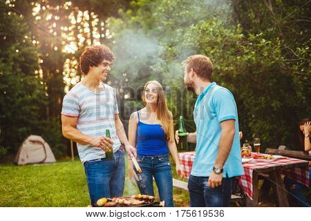 Friends enjoying drinks while making a barbecue togehter