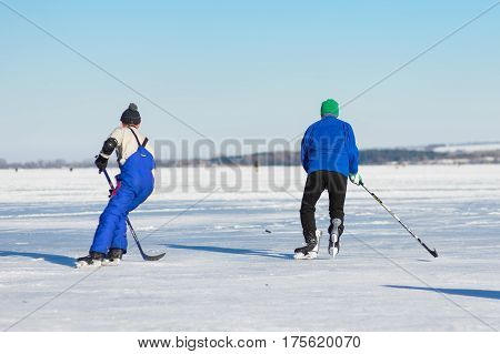 Dnepr Ukraine - January 22 2017: Mature man rushing to the pack while playing hockey on a frozen river Dnepr in Ukraine at January 22 2017