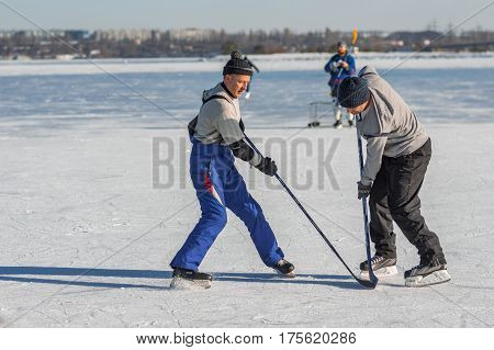 Dnepr Ukraine - January 22 2017: Mature man fighting for the pack while playing hockey on a frozen river Dnepr in Ukraine