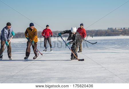 Dnepr Ukraine - January 22, 2017: Group of men playing hockey on a frozen river Dnepr in Ukraine