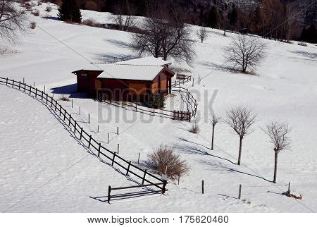 wooden chalet with fresh white snow in winter