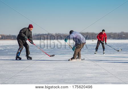 Dnepr Ukraine - January 22 2017: Amateur men playing hockey on a frozen river Dnepr in Ukraine at sunny weekend