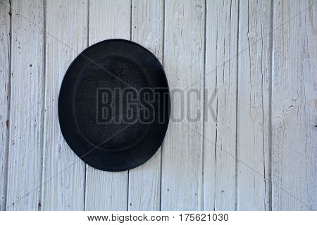 Of old black man's hat hangs on the left  on old white wooden wall