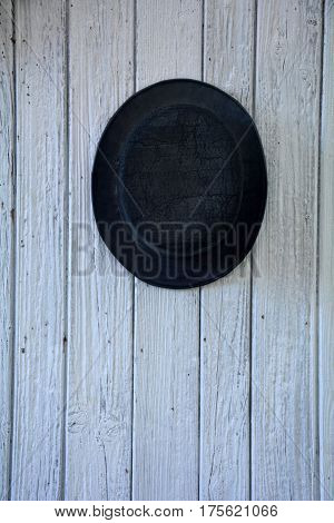 Of old black man's hat hangs in the middle  on old white wooden wall