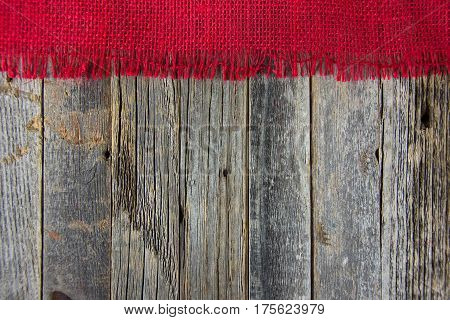 frayed red burlap border on weathered wood