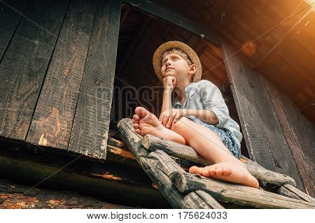 Dreming boy sits on the barn leader