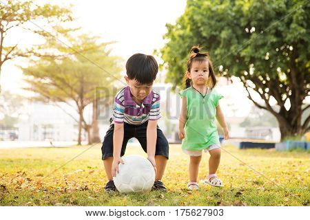 Boy and girl learning kick ball at the park in the evening.