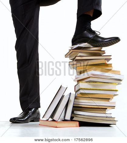 Businessman feet standing on book stack