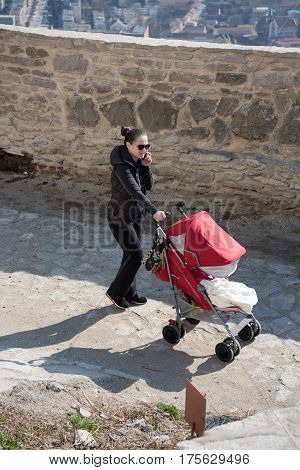 Deva, Romania - March 4, 2017, A woman walking with the baby stroller though the old medieval fortress