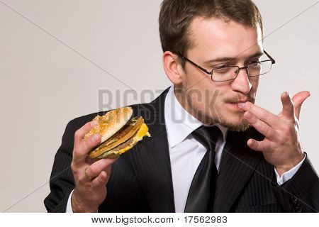 Young hungry businessman eating hamburger