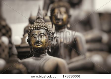 Row of Buddha statues at Ganagarama temple Colombo Sri Lanka. Black and white.Yellow selective colour.