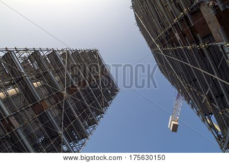 Construction site facility under construction with scaffolding and cranes