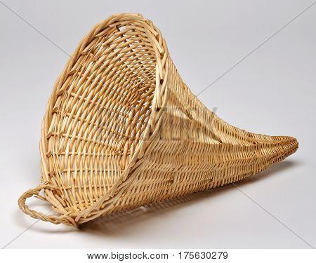 Empty wicker basket in the shape of cornucopia on white background