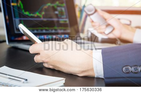Stock Broker with both hand on the phone making call to traders