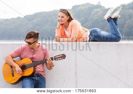 Love romance music talent passion dating concept. Guitarist and his muse. Young man playing guitar with girl lying on wall with scenery background.