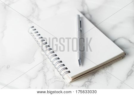 Silver metal pen on blank notebook page on marble desk
