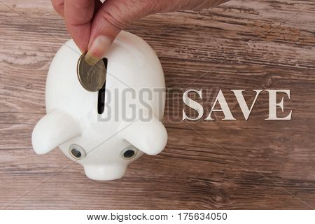 Adding to your saving A piggy bank and hand adding money with text Save