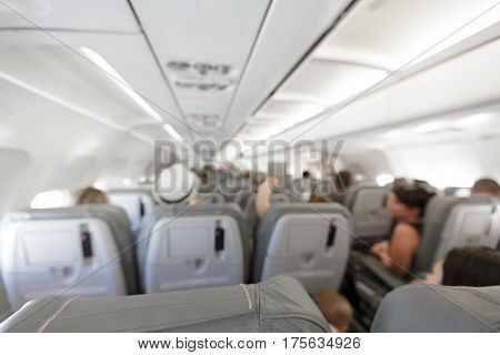 Blurred background: passenger on airplane. Interior of airplane with passengers on seats