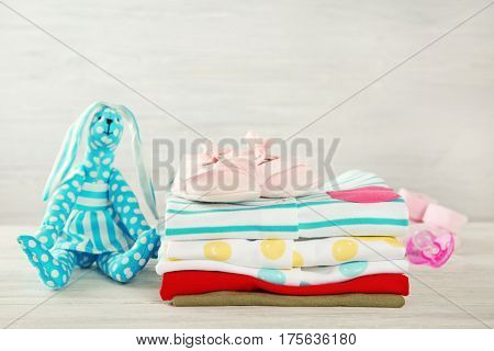 Pile of baby clothes on wooden table