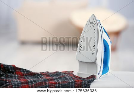 Electric iron and dress on ironing board in room
