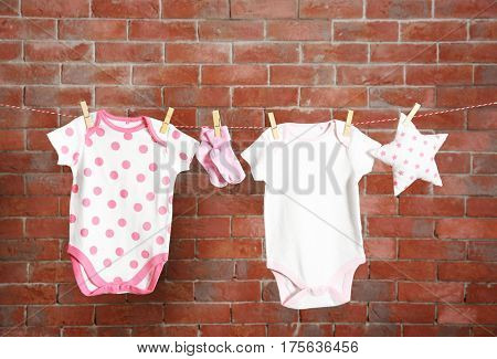 Clothesline with hanging baby clothes on dark brick-wall background
