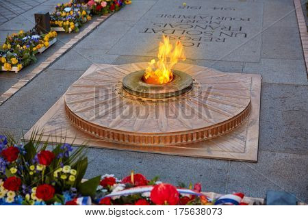 Unknown Soldier memorial flame under Arc de Triomphe in Paris France since 1921. Translation: a french soldier death for the nation