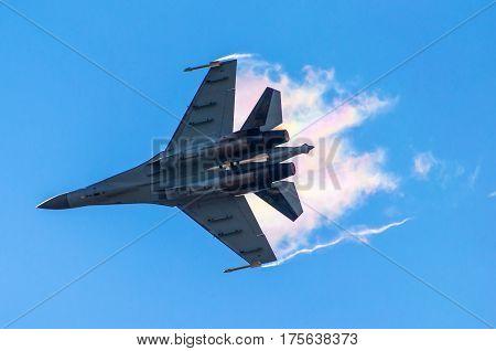 Battle fighter jet flying dives breaking clouds on a blue sky.