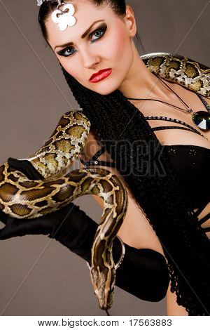 Gorgeous brunette holding boa constrictor poster