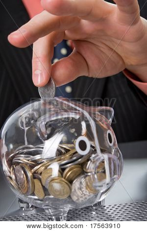Businessman's hand inserting coin into transparent piggy bank