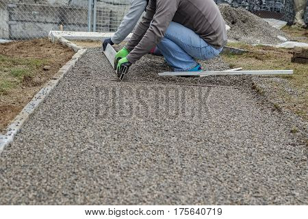 Worker leveling a metal screed board to gravel surface poster