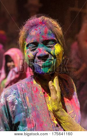 Nandgaon, India - March 21, 2016: Portrait of an unidentified woman with face smeared with colors during Holi celebration in Vrindavan, Uttar Pradesh, India.