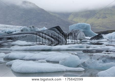 blue black and white and white icebergs floats on water separated from the Vatnajokull glacier in Iceland in the background green hills and cloudy sky