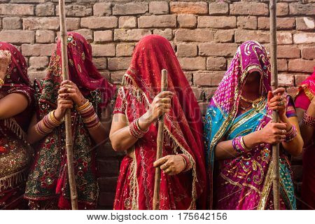 Nandgaon, India - March 18, 2016: Women beat up men with long sticks as a ritual in the Lathmar Holi celebration in Nandgaon, India. Holi is the most celebrated religious festival in India.