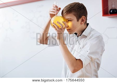 Interesting science. Curious smart nice boy holding a flask and looking at it while working in the lab