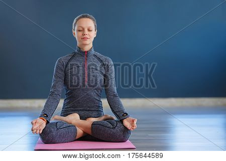 Beautiful young woman sitting in Lotos pose. woman practicing meditation in yoga hall after hard day, sitting in a prayer position on the pink yoga mat. Time for Yoga and relaxation. Closed eyes.