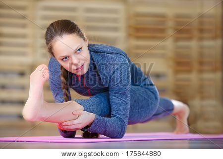 Woman doing yoga exercise called Revolved Head-to-Knee Pose - stage 2, Sanskrit name: Parivrtta Janu Sirasana, this pose helps with emotional calming during time of intense hormonal shifts. Pink yoga mat and blue sportwear.