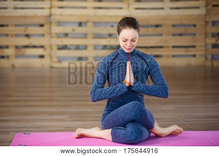 Sporty young woman doing yoga practice on pink yoga mat - concept of healthy life and natural balance between body and mental development. Blue sportwear.