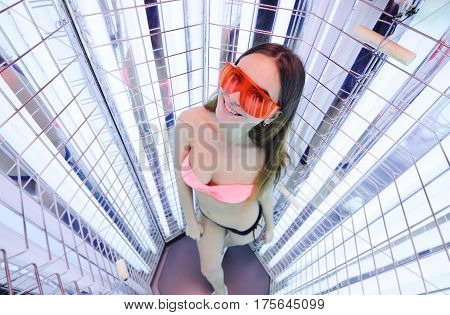 pretty girl on the background of the device for the treatment of light. phototherapy.Woman tans in the solarium
