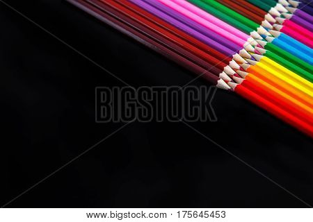 colored pencils isolated on black background lying in opposite corners. Angle. Drawing and painting. Hobbi. Artist. Art and design.