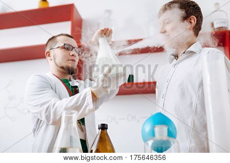 Chemistry lesson. Smart professional male teacher wearing a white coat and holding a chemical flask while showing a chemical reaction to his students