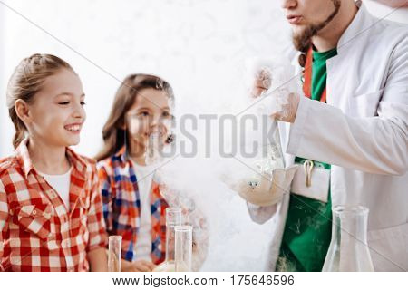 Fascinated by the experiment. Delighted positive cute girls smiling and being surrounded by chemical smile while watching the chemical experiment