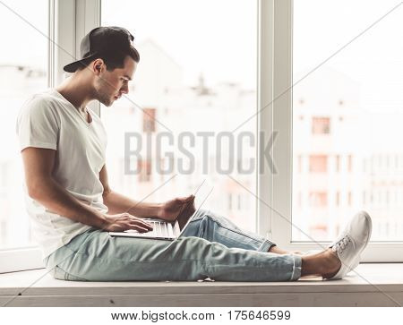 Stylish young man in cap is using a laptop while sitting on the window sill