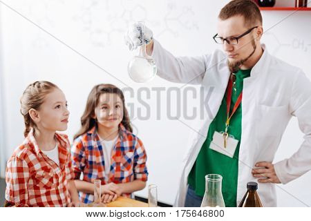 Interesting chemistry. Serious thoughtful bearded man holding a chemical flask and looking at the liquid in it while showing the children an experiment