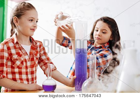 Involved in the activity. Nice smart thoughtful girls standing around chemical reagents and working with them while being in the laboratory
