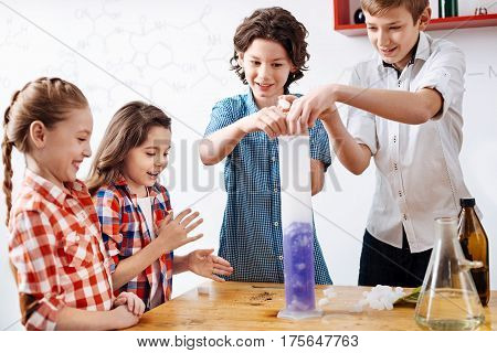 What will happen. Positive delighted nice boys standing in front of the table and putting some chemical reagents to a retort while conducting an experiment