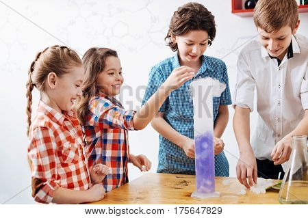 Young scientists. Cheerful smart cute girl putting something to the chemical retort and smiling while enjoying her time in the lab