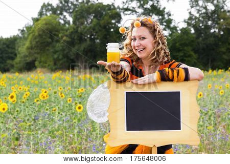 A woman dressed as a bee leaning against a sign and holding a glass of honey in her hand