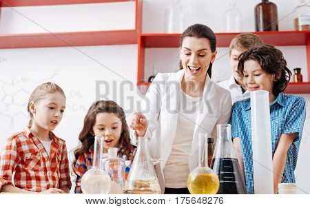 Chemical experiments. Happy beautiful chemistry teacher being surrounded by children and putting something to a flask while conducting a chemical experiment