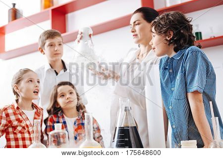 Optional chemistry lesson. Intelligent curious smart children standing around the table and looking at the chemical flask while waiting for some chemical reaction to happen